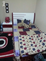Red queen bed with side table and wardrobe