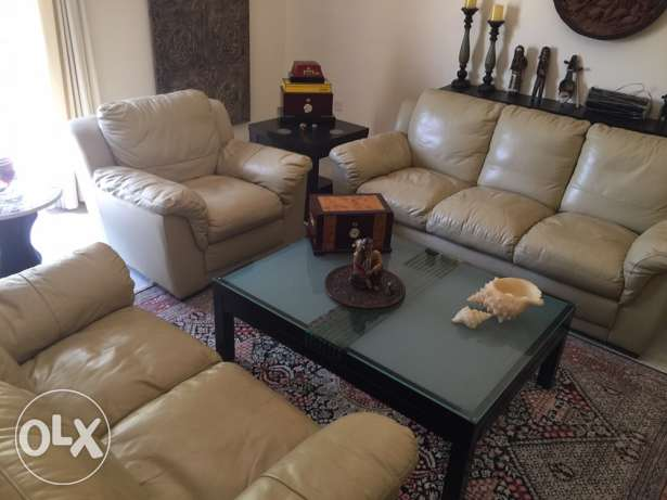 beige leather sofa set with a center table