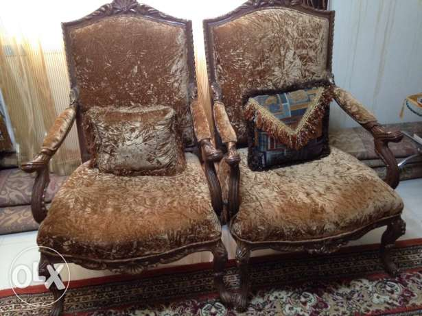 exclusive two golden brown velvet chairs with two pillows.